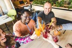 Een bedrijf van jongeren die pret hebben, drinkend dranken, cocktails, sappen in een koffie samenkomende beste vrienden stock foto's