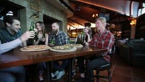 Een bedrijf van jongeren rust in een bierrestaurant stock videobeelden