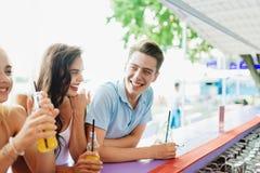 Een bedrijf van knappe vrienden, het drinken gele cocktails die en het socialiseren bij de bar in de aardige de zomerkoffie lache stock afbeeldingen