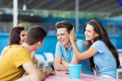 Een bedrijf van knappe vrienden lacht en zit bij de lijst in de aardige de zomerkoffie Vermaak, die hebben stock afbeeldingen