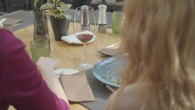 Een bedrijf van niet erkende meisjes dineert in een duur restaurant terwijl het zitten met hun ruggen aan de camera stock footage
