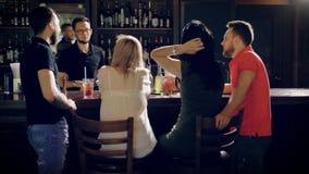 Een bedrijf van vrienden bevindt zich dichtbij de bar en het spreken, mannen en vrouwen die cocktails willen drinken, communicere stock video