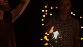 Een bedrijf van vrienden danst bij nacht met de lichten van Bengalen in hun handen stock footage