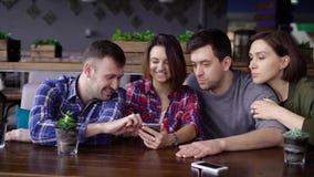Een bedrijf van vrienden die in een restaurant zitten en op hun maaltijd wachten, bekijkt met vreugde en lach foto's op mobiel stock footage