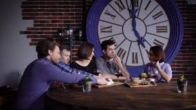 Een bedrijf van vrienden heeft samen een goede tijd bij het restaurant, heeft diner en neemt nota van de recente stijging van stock footage