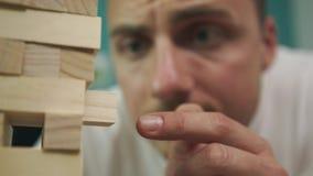 Een bedrijf van vrienden speelt een houten toren in een comfortabele woonkamer stock footage