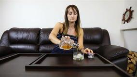 Een bedrijfsdame goot alcohol van een karaf in een glas met ijs en dronk stock videobeelden