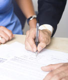Een bedrijfsmens ondertekent de overeenkomst royalty-vrije stock fotografie