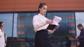 Een bedrijfsvrouw bekijkt discussienota's terwijl een zakenman en een bedrijfsvrouw haar behandelen stock footage