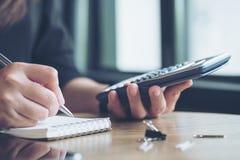 Een bedrijfsvrouw die, calculator gebruiken en op notitieboekje in bureau schrijven werken Royalty-vrije Stock Foto's