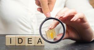 Een bedrijfsvrouw die een houten blok met een een gloeilampenidee of inspiratie houden Generatie van innovatieve bedrijfsideeën c royalty-vrije stock foto