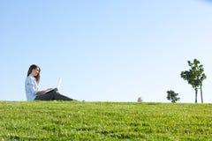 Een bedrijfsvrouw op laptop op een gebied Stock Fotografie