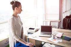 Een beeld die van bezige vrouw zich dichtbij haar bureaulijst en stoel bevinden Zij bekijkt de lijst met een ernstig gezicht stock fotografie