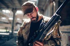 Een beeld die van strijder zich in een hangaar bevinden en neer zijn geweer bekijken Hij maakt het schoon en bereidt het voor om  royalty-vrije stock afbeeldingen