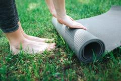 Een beeld van de vrouwelijke benen en de handen van ` s Het meisje rolt carimate op Sluit omhoog Yoga en Pilates-Concept royalty-vrije stock foto
