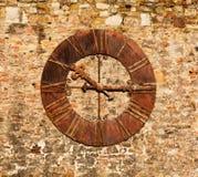 Een beeld van een zeer oude klok op een bakstenen muur Stock Foto's