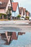 Een beeld van familiehuizen met een bezinning in water worden genomen dat stock afbeeldingen