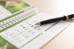 Een Beeld van een kalender en een pen stock fotografie