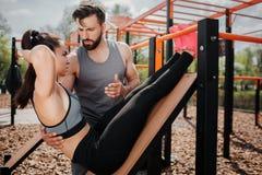 Een beeld van meisje doet abs oefening op de sportbank De oefening is zeer intensief De kerel adviseert haar royalty-vrije stock afbeeldingen