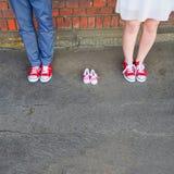 Een beeld van volwassenen in rode tennisschoenen naast babypaar tennisschoenen Stock Foto