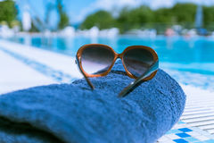 Een beeld van Zonglazen en handdoek, dichtbij zwembad Royalty-vrije Stock Afbeelding