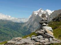 Een beeldhouwwerk van kiezelstenen en de Zwitserse bergen op de achtergrond stock afbeeldingen