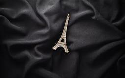 Een beeldje van de Toren van Eiffel op een zwarte stoffenachtergrond Hoogste mening royalty-vrije stock fotografie