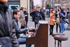 Een begaafde dakloze musicus speelt de piano in de straat om wat geld te verdienen royalty-vrije stock afbeeldingen