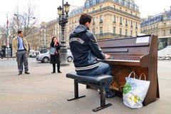 Een begaafde dakloze musicus speelt de piano in de straat om wat geld te verdienen stock fotografie
