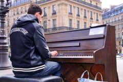 Een begaafde dakloze musicus speelt de piano in de straat om wat geld te verdienen royalty-vrije stock fotografie