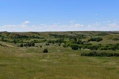 Een begraafplaats, een weg, en boerderijen in een vallei Royalty-vrije Stock Foto