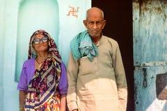 Een bejaard Hindoes paar die zich buiten hun landelijk huis, Rajasthan, Noordelijk India bevinden stock foto's