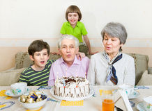 Een bejaard paar blaast uit kaarsen op een cake stock foto