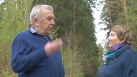 Een bejaard paar spreekt emotioneel op een gang in het park Een mens zegt iets en maakt gebaren met zijn handen stock videobeelden
