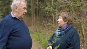 Een bejaard paar spreekt op een gang in het park Zweer, kom de verhouding te weten stock video