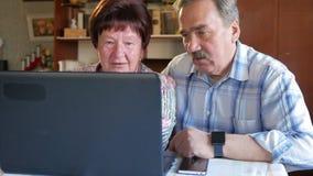 Een bejaard paar zit thuis bij laptop Een vrouw leest nieuws, zit een mens met een snor naast hem en spreekt stock video