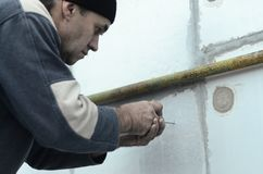 Een bejaarde arbeider creeert gaten in de uitgebreide polystyreenmuur voor de verdere boring en de installatie van een paraplupen royalty-vrije stock fotografie