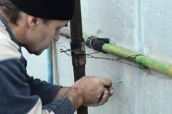 Een bejaarde arbeider creeert gaten in de uitgebreide polystyreenmuur voor de verdere boring en de installatie van een paraplupen stock afbeeldingen