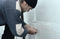 Een bejaarde arbeider creeert gaten in de uitgebreide polystyreenmuur voor de verdere boring en de installatie van een paraplupen stock fotografie