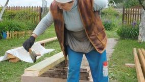 Een bejaarde behandelt een houten straal met een speciale oplossing voor bescherming tegen vorm stock videobeelden