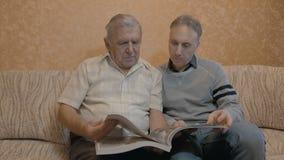 Een bejaarde bekijkt een boek met zijn volwassenezoon stock footage