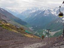 Een bejaarde beklimt omhoog met een trekkingspool op een hoge berg concept een gezonde levensstijl voor oudere mensen Rusland, El royalty-vrije stock afbeelding