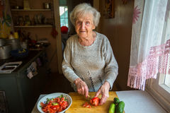 Een bejaarde bereidt een maaltijd voor stock foto's