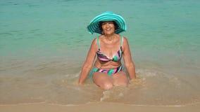 Een bejaarde in een blauwe hoed in een helder zwempak zit op het strand en het glimlachen reis concept stock footage