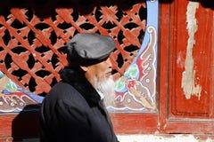 Een bejaarde Chinese mens met een kenmerkende baard langs de straat in het dorp van Shigu, Yunnan, China stock foto's