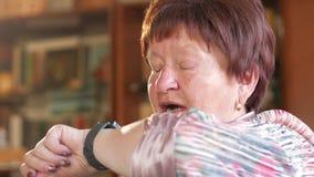 Een bejaarde controleert de berichten op een slim horloge Zij leest herinneringen en spreekt de uitdrukking voor een onderzoek da stock video