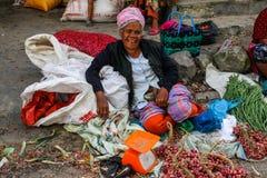 Een bejaarde dame in een interessante hoed verkoopt groenten bij de lokale Indonesische authentieke en kleurrijke straatmarkt stock fotografie