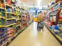 Bejaarde dame die in een kortingsopslag winkelen Stock Afbeeldingen