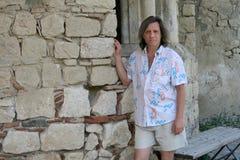 Een bejaarde dichtbij de oude steenmuur Stock Fotografie