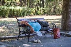 Een bejaarde die blootvoets op een bank in het stadspark liggen en in het midden van de dag in Burgas/Bulgaria/08/14/2016 slapen royalty-vrije stock afbeelding